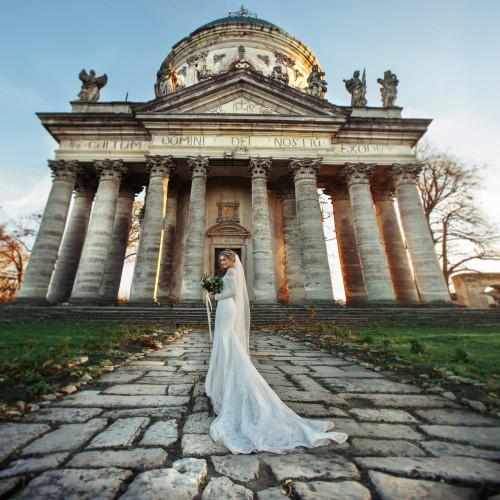 Beautiful blonde princess bride posing near baroque christian church